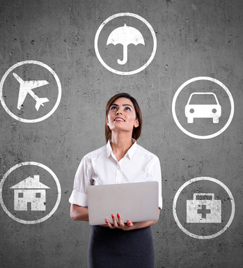 Young businesswoman working on laptop and looking at insurance symbols on wall.